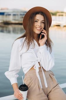 電話で話して、夕暮れ時の暖かい夏の日にビーチフロントを歩いているスタイリッシュな女性
