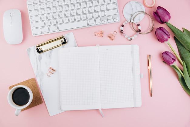 Женский рабочий стол с тюльпанами, клавиатурой, золотыми клипсами на розовом