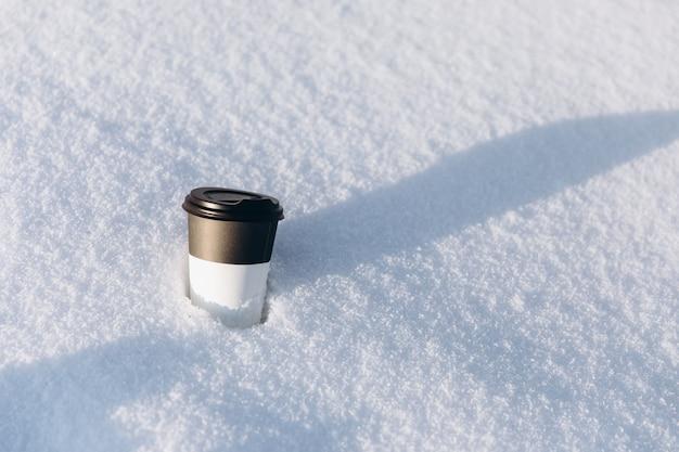 冬のコンセプト。雪の中でコーヒーの黒と白のカップ。