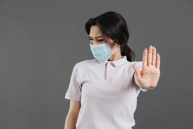 Женщина в медицинской защитной маске показывает жест остановки коронавируса.