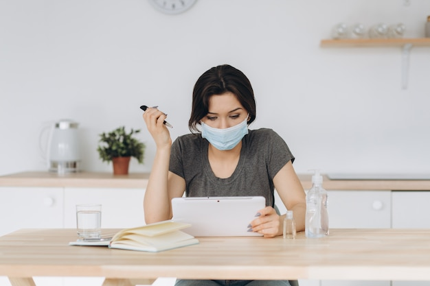 コロナウイルス。保護マスクを着用して自宅で仕事若いビジネス女性。保護マスクを身に着けているコロナウイルスの検疫の女の子。消毒ジェルと水で自宅で仕事をする
