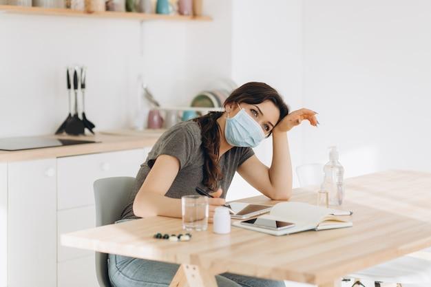 口と鼻を覆うコロナウイルスを広めるコロナウイルスウイルス感染症の拳で咳をする防護マスクの女性。自宅検疫でキッチンに座っている頭痛病気患者