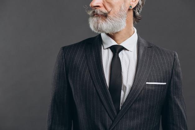 Обрезанное крупным планом фото шикарного мужского, роскошного, модного, богатого, богатого, острого, хорошо одетого в бордовые аксессуары. клетчатая куртка. умный хипстерский дедушка, фиксирующий манжеты на серой стене.