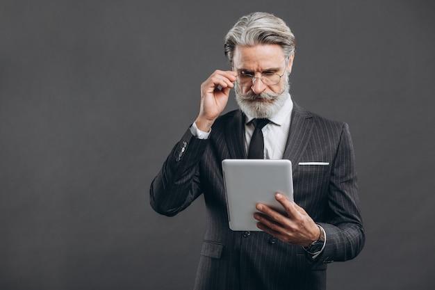 ビジネスとファッショナブルなひげを生やした灰色の壁に金のクレジットカードでタブレットで買い物をする灰色のスーツの成熟した男。