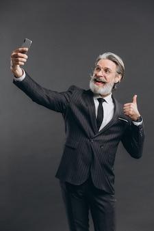 Бизнес и модный бородатый зрелый человек в сером костюме делают селфи на серую стену.