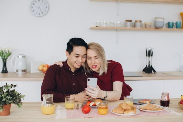 アジア人男性と彼の白人の金髪女性は朝食を持っています。彼らは一緒にキッチンで時間を過ごし、電話でビデオを見ます。