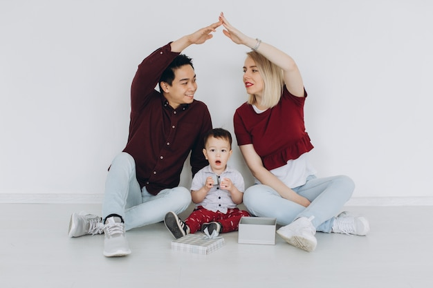 Новый дом жилой дом купить квартиру концепция. многокультурная семья с сыном, сидя на полу, кавказская мама и азиатский папа, делая крышу с руками над головой