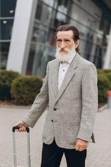 スーツケースと市内地図を運ぶ灰色のひげを生やした年配の男性が空港の建物に沿って歩いています。彼はしんみりと脇を見ています。右側にスペースをコピー