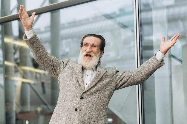 Старший седобородый мужчина машет руками от счастья и с радостью уходит на пенсию