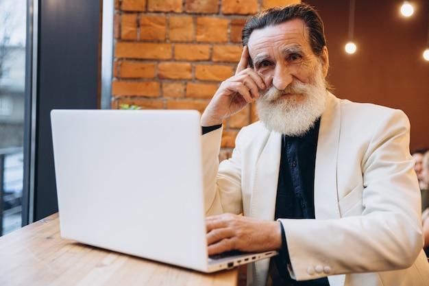Задумчивый старший мужчина, с белой бородой, улыбается, глядя на свой ноутбук. пожилой кавказец. пожилой человек и новые технологии