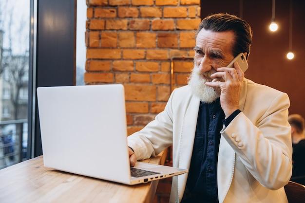 Задумчивый старший мужчина, с белой бородой, улыбается, глядя на свой ноутбук и принимая по телефону. пожилой кавказец. пожилой человек и новые технологии