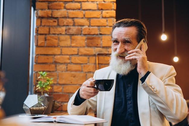 Портрет бородатого кофе старшего человека выпивая и использования умного телефона в кафе. портрет счастливого серого бородатого человека сидя в кафе.