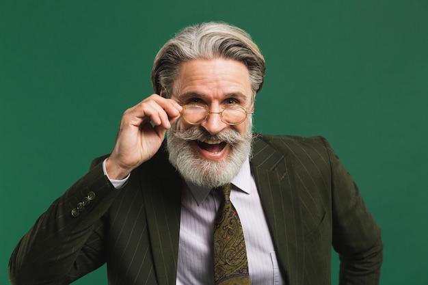 スーツを着たひげを生やした中年教師が彼の手でメガネを保持し、緑の壁で楽しい目を点滅させる