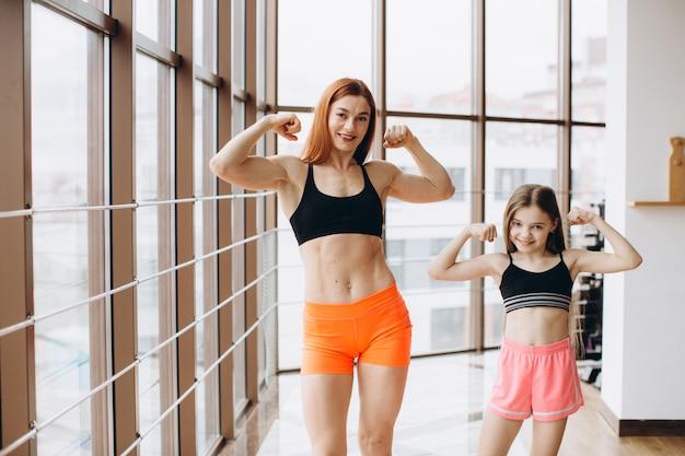 Красивая сильная женщина и очаровательная маленькая дочь показывают их бицепс и улыбается во время тренировки в тренажерном зале