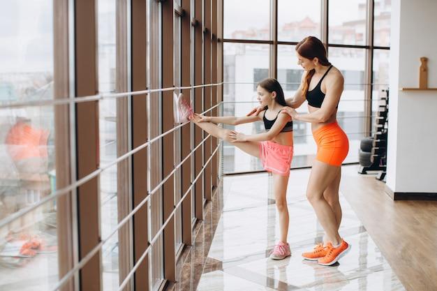 Сильная мама и ее дочка занимаются фитнесом, занимаются спортом и растягиваются в тренажерном зале