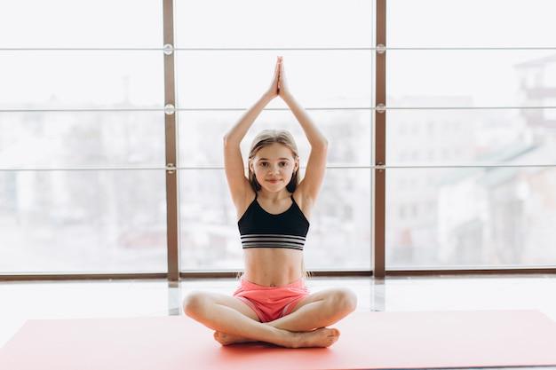Очаровательная маленькая девочка улыбается, занимаясь йогой в фитнес-зале