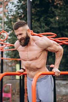 屋外ストリートジムのでこぼこのバーで腕立て伏せを行う強い筋肉のひげを生やした男。トレーニングライフスタイルのコンセプトです。