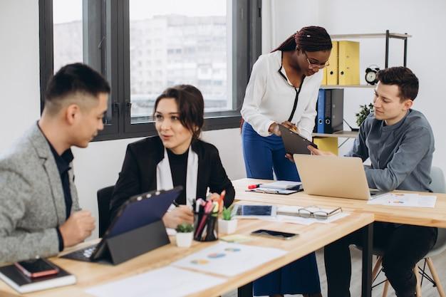 オフィスでのブリーフィング中に自分のインターネットのウェブサイトを議論するフォーマルな服装の男性と女性の専門家の多文化グループ。ビジネスプロジェクトのブレーンストーミングに協力している多様な若者