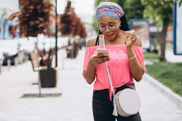 Афро-американская девушка, используя свой мобильный телефон на улице