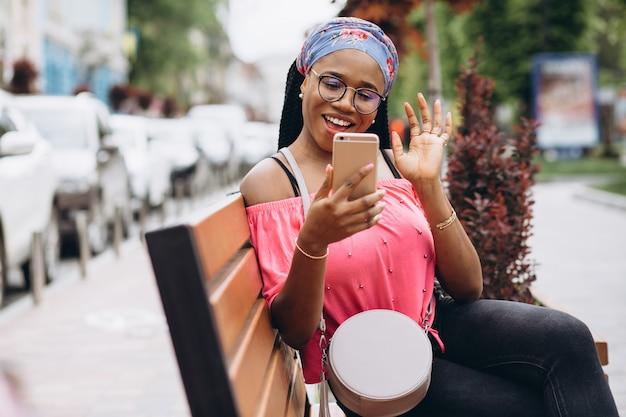 Афро-американская девушка, используя ее мобильный телефон, сидя на деревянной скамье