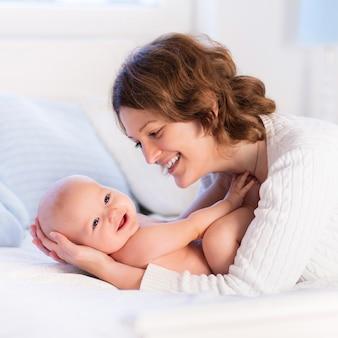 母親と赤ちゃんは白いベッドの上