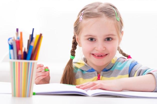 Маленькая смешная девочка играет с маркерами за столом