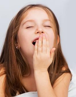 Маленькая девочка зевает