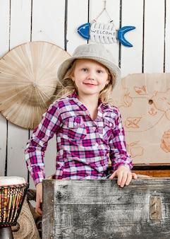 Милая маленькая девочка в шляпе сидит в груди