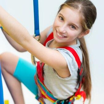 Активная маленькая девочка в ремнях безопасности на стене для скалолазания