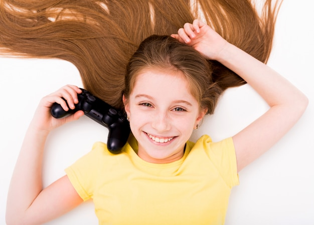 Девушка растягивается на полу с джойстиком в руке