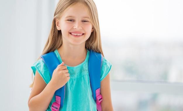バックパックで学校に行く準備ができている少女