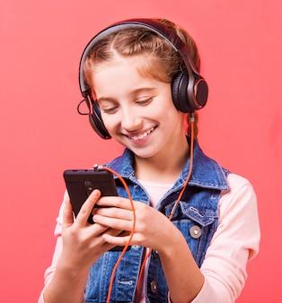 Девочка-подросток слушает музыку в больших наушниках