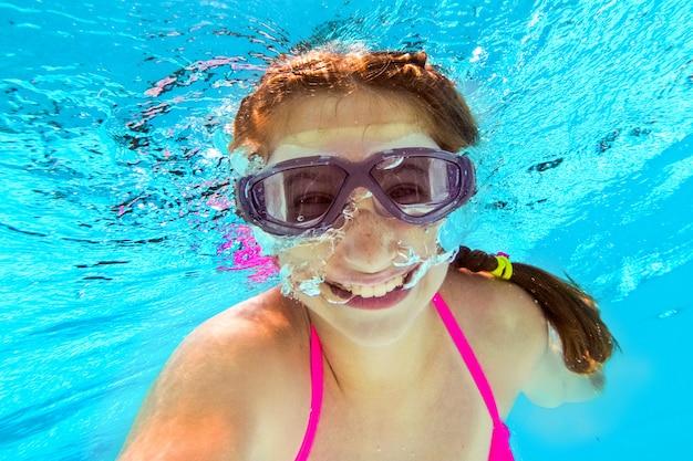プールで水中泳いでいる少女の笑顔