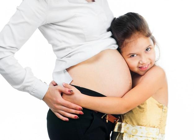 Маленькая девочка обнимает живот