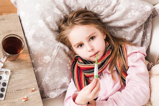病気の女の子が温度を測定