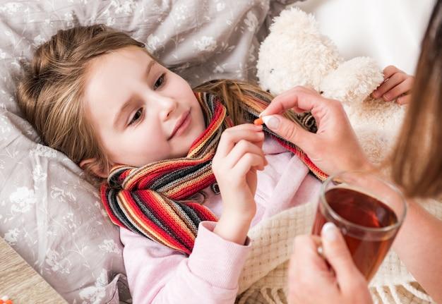 病気の娘に枕を与える母