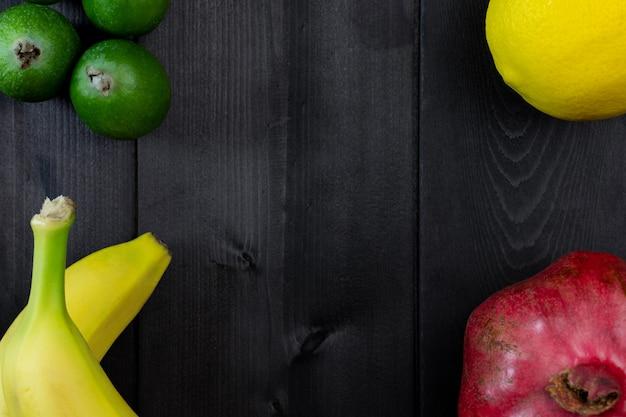 木製の背景に果物。ザクロ、レモン、フェイジョア、バナナ。