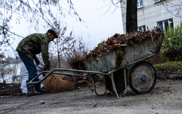 ほうきの庭を掃除する用務員