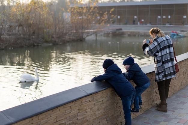 Мама и сын смотрят на птиц, плавающих в пруду.
