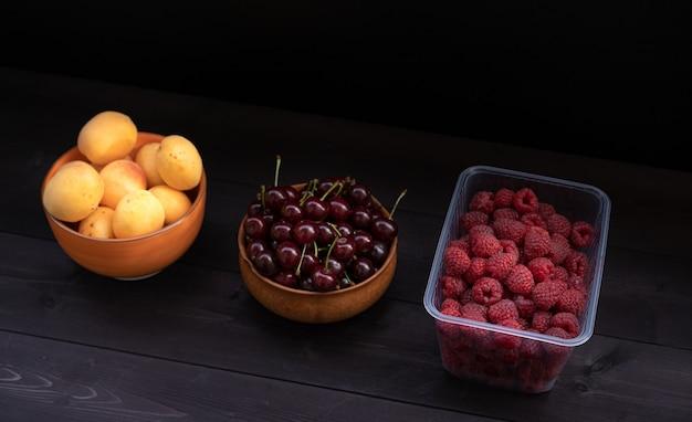 Малины вишни и абрикосы на деревянном