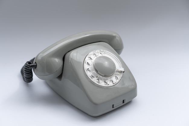 Дисковый телефонный аппарат на белом фоне