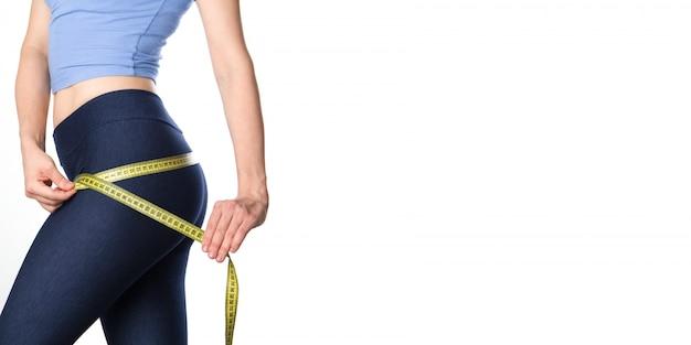 女性は彼女の体を測定します。フィットネス女性バナー。コピースペース。