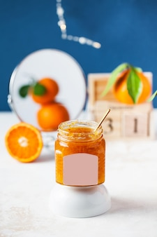 背景の柑橘類のタンジェリンジャムは、新鮮なオレンジ色の果物を反映しています。