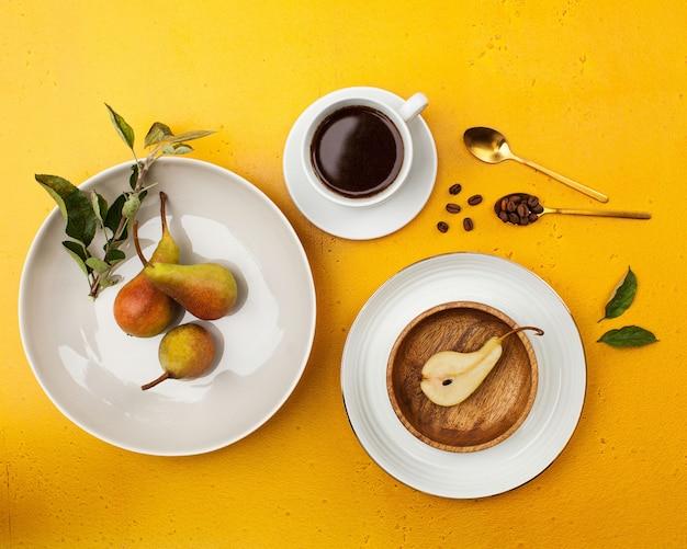 Флэтлай с тарелками, кофейной кружкой, кофейными зернами и свежими грушами. понятие минимализма.