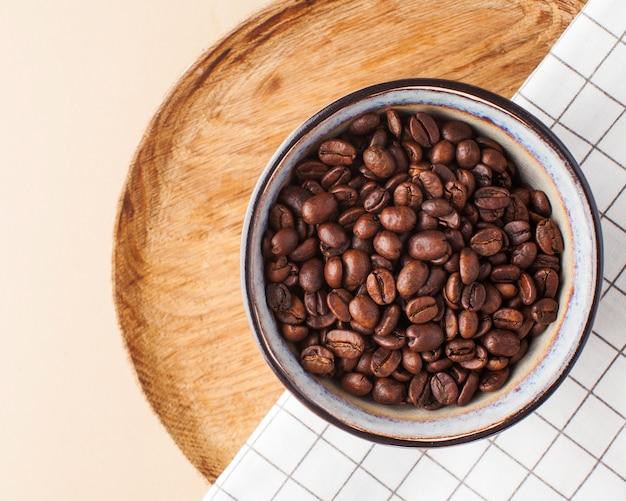 Кофейные зерна арабики в керамическом шаре на деревянном подносе на коричневой предпосылке. горизонтальные фото с пространством для текста. для кофеен и кафе.