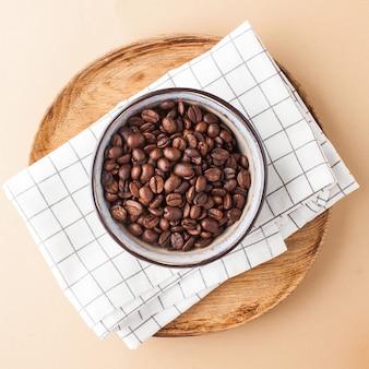 Кофейные зерна арабики в керамическом шаре на деревянном подносе на коричневой предпосылке. квадратное фото для кафе и кафе.