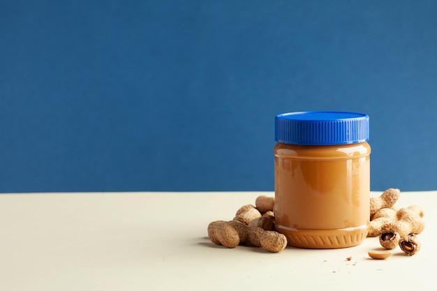 Закрытая банка арахисового масла, арахис в скорлупе.
