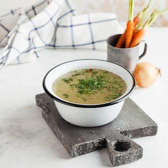 Домашний бульон в белый шар на деревянной доске с овощами. концепция здорового питания.