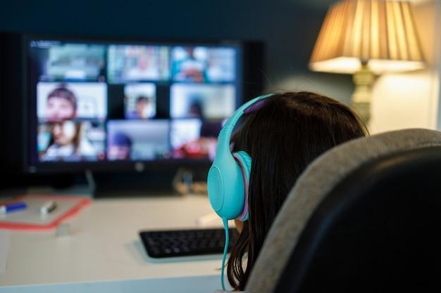 自宅でレッスンを受けるコンピューターの画面の前にヘッドセットを持つ少女。自宅で学校。