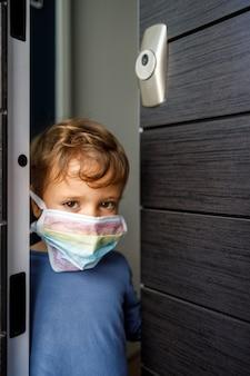 虹の色で描かれたマスクを持つ彼の家のドアで小さな男の子